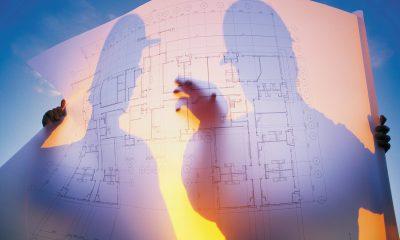 Två byggarbetare bakom en ritning i solen