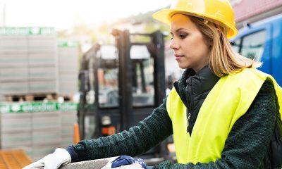 Kvinnlig byggarbetare jobbar på en byggarbetsplats.