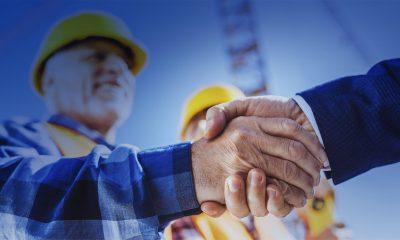 Byggarbetare skakar hand med man i kostym när projektet är slut.