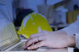Man vid laptop och bygghjälm använder Byggnet.